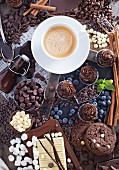An arrangement of chocolate featuring cookies, cupcakes, chocolate chips, syrup, marshmallows, blueberries, cinnamon sticks and coffee