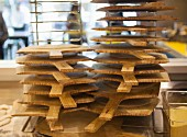 A stack of pizza boards on a rack in a pizzaria