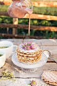 A stack of nut waffles with chamomile tea on a garden table