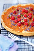 Pumpkin tart with orange marmalade, raspberries and corn flowers