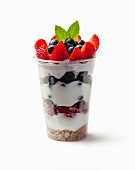 Muesli in a plastic cup with yoghurt and berries on a white surface