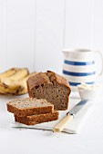 Freshly baked banana bread, sliced, on a porcelain board