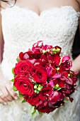 A bride wearing a lace dress holding a bouquet of red flowers