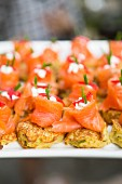 Salmon with cream cheese and red peppers on pancake bites