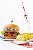 A Greek-style hamburger with a spicy corn cob and sparkling water
