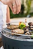Vegan burgers and aubergine & tofu kebabs on a barbecue