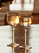 Two elegant glasses of white wine on a table