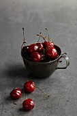 Red cherries in an old metal cup