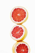 Three pink grapefruit halves stacked on top of each other