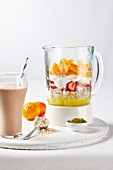 Yoghurt shake with fruits in a glass and layers of ingredients in a blender