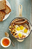 Fried eggs with sausages and fried potatoes, wholemeal toast and apricot jam