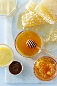 Honey in a glass bowl with a honey spoon, honey comb and sweet sauces on a white surface