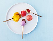 Colourful scoops of ice cream on a white plate with golden spoon