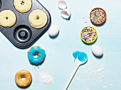 Doughnuts in a baking tin with ingredients and sprinkles