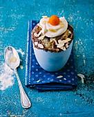 A white chocolate mug cake with poppyseeds and a mascarpone topping