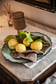 An arrangement of lemons on a grey linen napkin