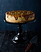 Cheesecake with pistachio nuts and chocolate glaze on a cake stand