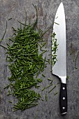A kitchen knife next to freshly chopped chives