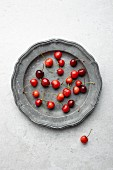 Fresh cherries on a vintage metal plate (seen from above)