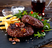 Venison burgers with tomato and onion salsa, chips and rocket