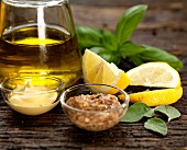 Ingredients for salad dressing with olive oil, Dijon mustard, hot mustard, lemon, basil and sage
