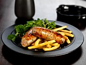 Fried pork and ale sausages with French fries and watercress