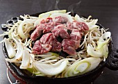 Lamb with beansprouts and onions in a ceramic pot (Japan)