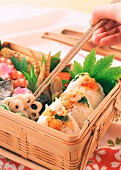 A selection of savoury Japanese food in a wooden basket