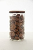 Roasted chestnuts in a screw-top jar on a white surface