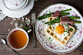 A savoury waffle with a fried egg, asparagus wrapped in ham and chives