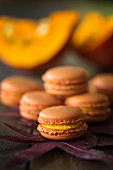 Pumpkin macaroons on autumn leaves