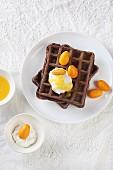 Cocoa waffles with orange sauce, ricotta and kumquats