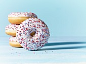 Doughnuts with white icing and colourful sugar sprinkles