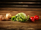 Cos lettuce, tomatoes and onions on a wooden surface