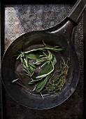 Fresh sage, rosemary and thyme in an antique pan (seen from above)