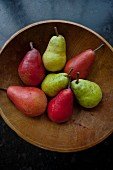Various types of pears in a wooden bowl