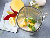 Ingredients for a shake with coconut milk, mango, basil and lemon
