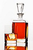 Whiskey in a glass and a bottle on a white surface