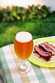 A glass of Largo on a garden table with a plate of beef on a cabbage salad