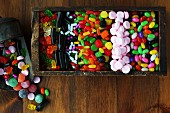 Various coloured sweets in a wooden box (seen from above)