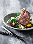 Knuckle of pork with root vegetables and kale