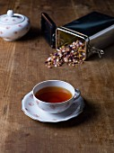 A cup of herbal tea and a tine of tea leaves on a wooden table