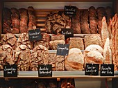 Various types of bread on shelves in a bakery