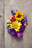 Verschiedene Sommerblumen auf Holztisch (Draufsicht)