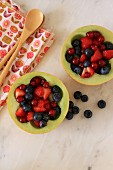 Summer berry salad served in hollowed out melon halves