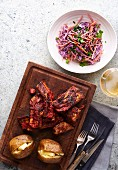 Spicy Cajun ribs with baked potatoes and coleslaw