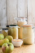 Jars of apple sauce and fresh apples