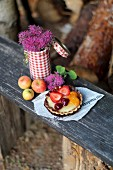 A fruit tartlet on a wooden bench in a garden