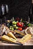 A cheese platter with bread, spices, grapes, tomatoes and wine