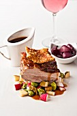 Roast pork with crackling on a bed of vegetables
